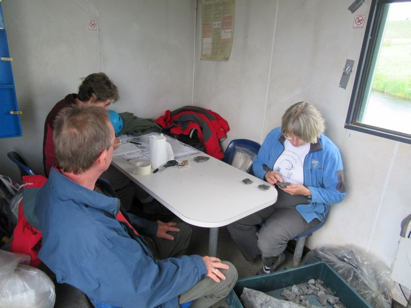 When the weather was unfavourable, we sat in the hut packing and labeling specimens.  Here, Jenny Clack identifies the bones, Rob Clack packs them in acid-free paper and foam or bubble film, and Janet Sherwin records the details.